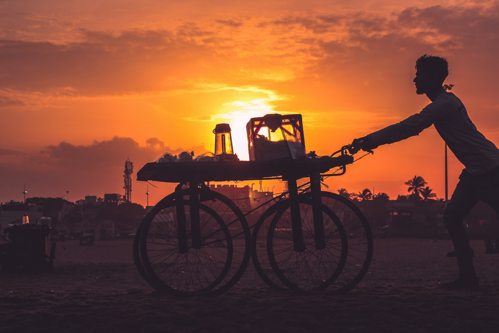 silhouette of bicycle on beach during sunset