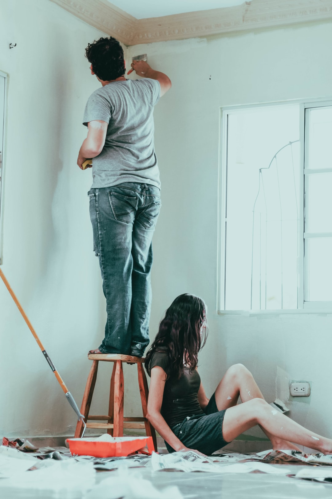 Pareja pintando su nuevo hogar.