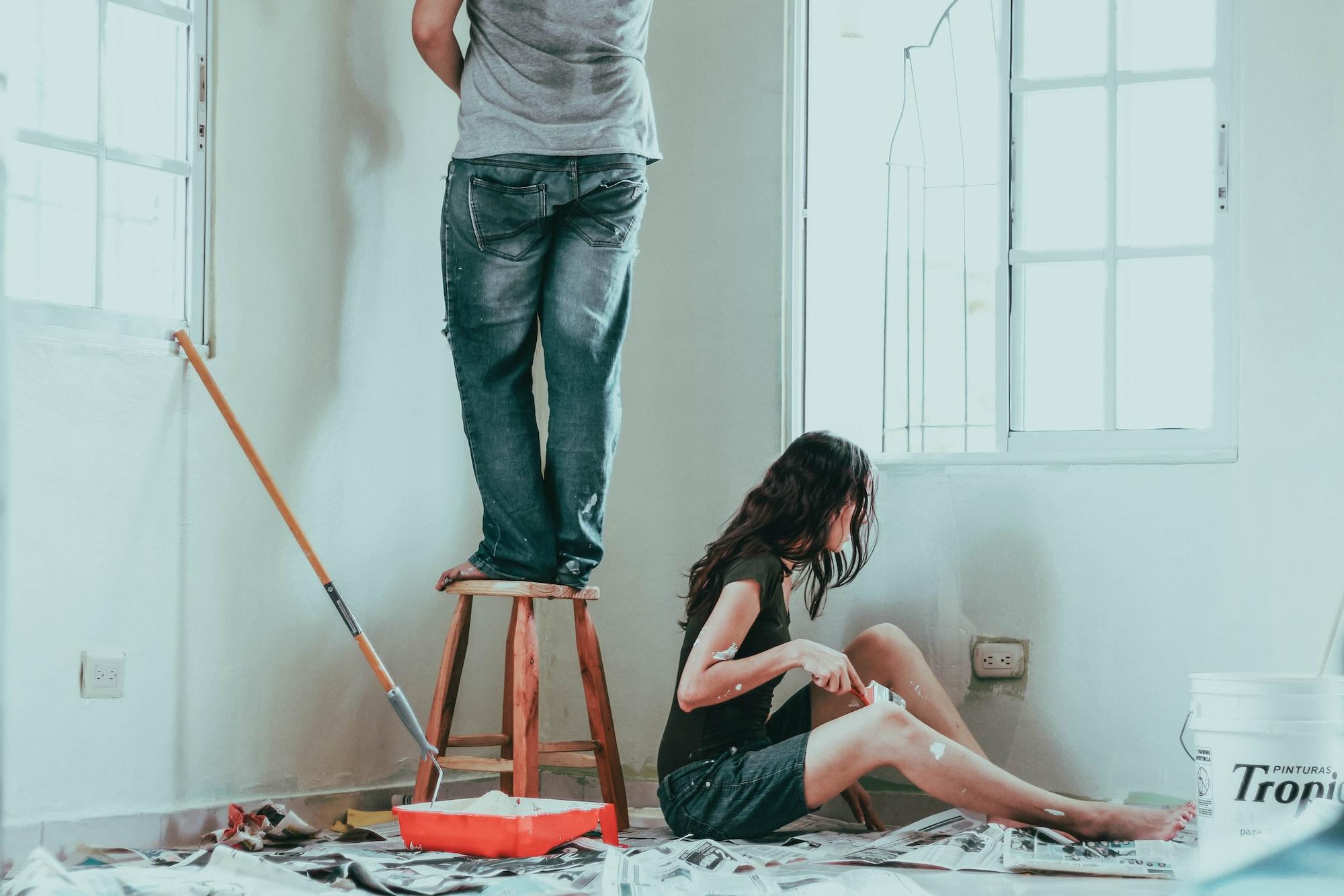 Casal pintando um cômodo de branco, mulher sentada e as pernas de um homem que pinta aparentemente um local mais alto .