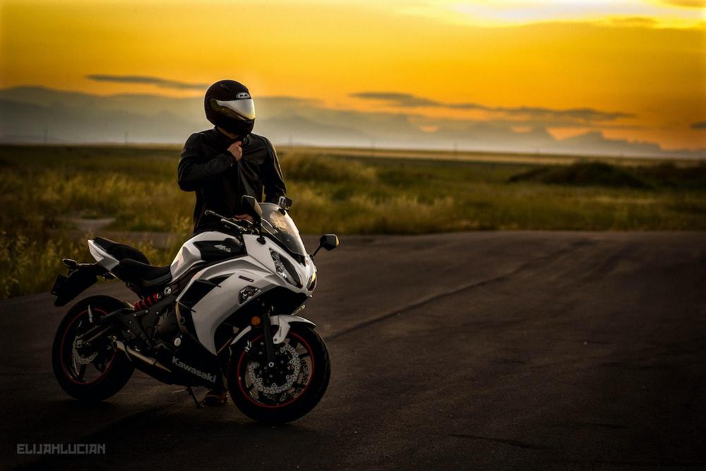 man in black jacket riding white sports bike on road during daytime