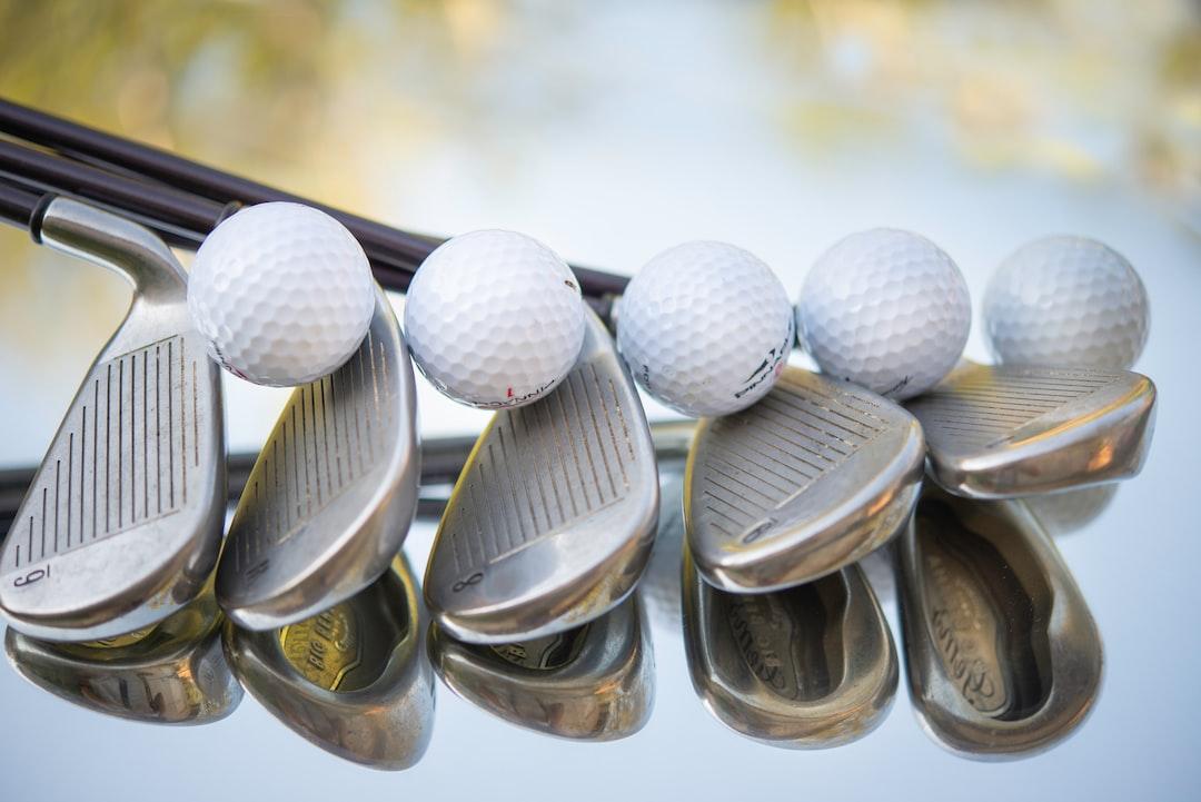 Golf wedges and balls shot close up.