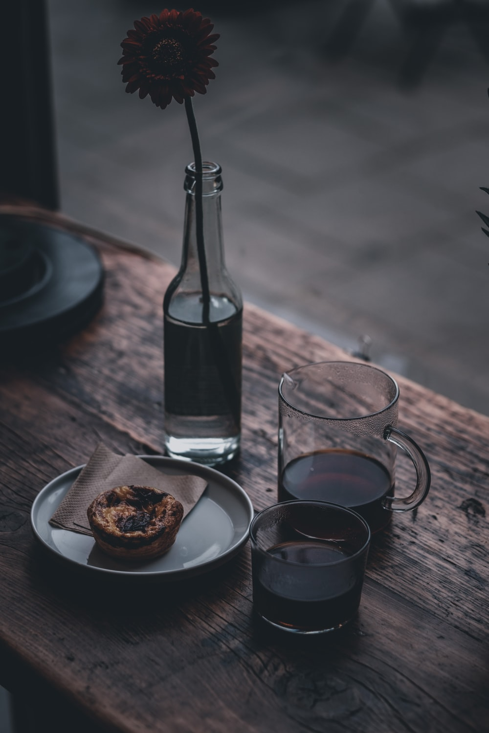clear glass bottle beside clear drinking glass on brown wooden table