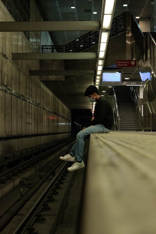 man in black jacket and blue denim jeans sitting on train rail