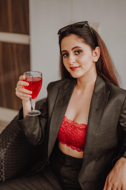 woman in black blazer holding red wine glass