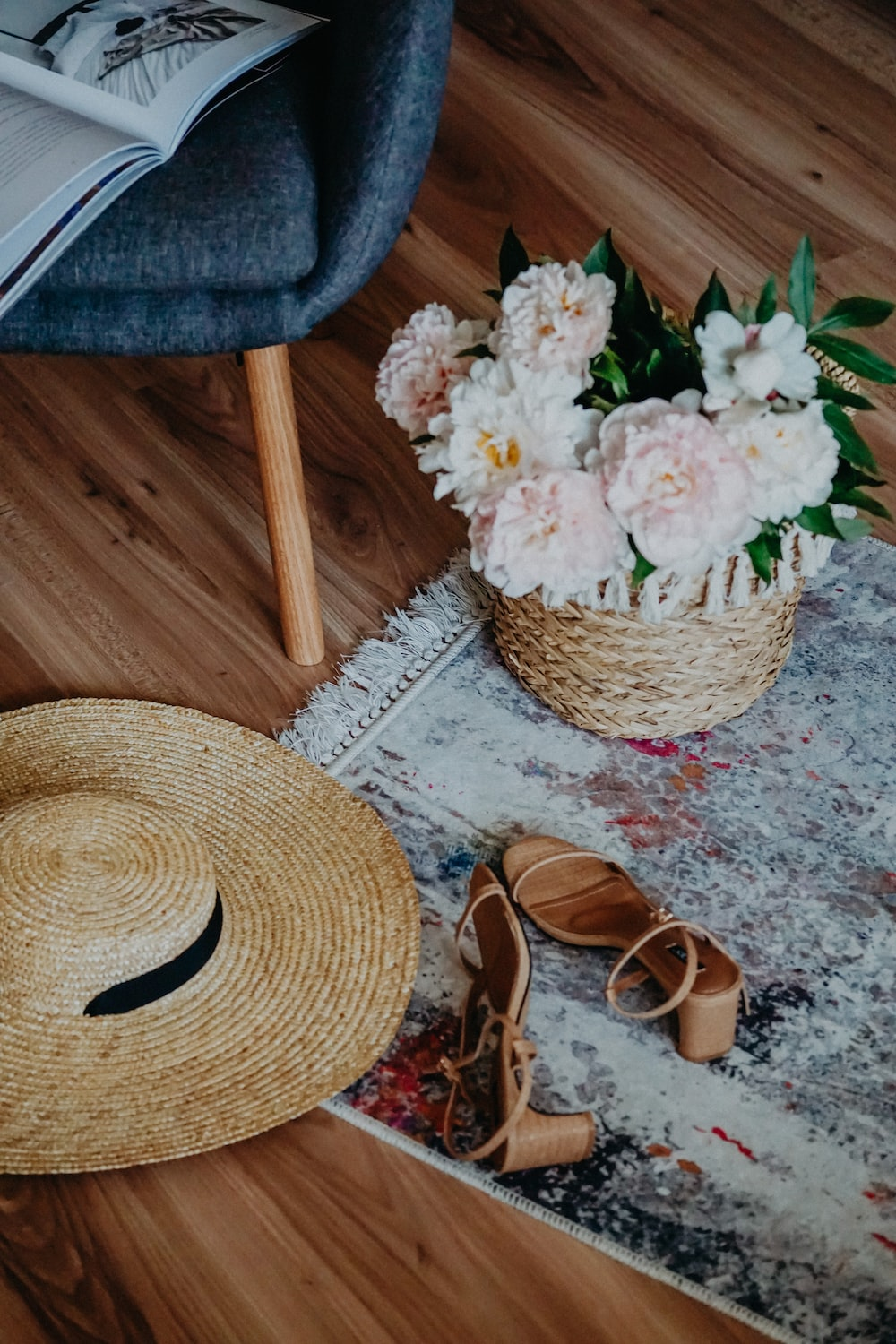 brown straw hat beside white flowers on brown wooden table