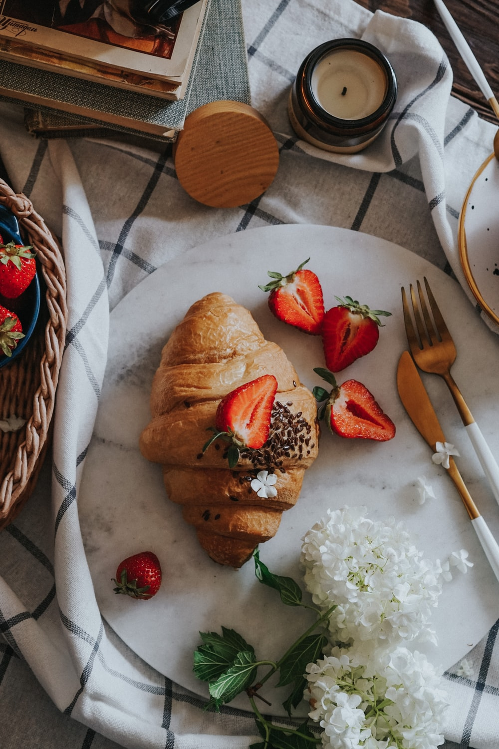 bread with sliced strawberries and green leaves on white ceramic plate