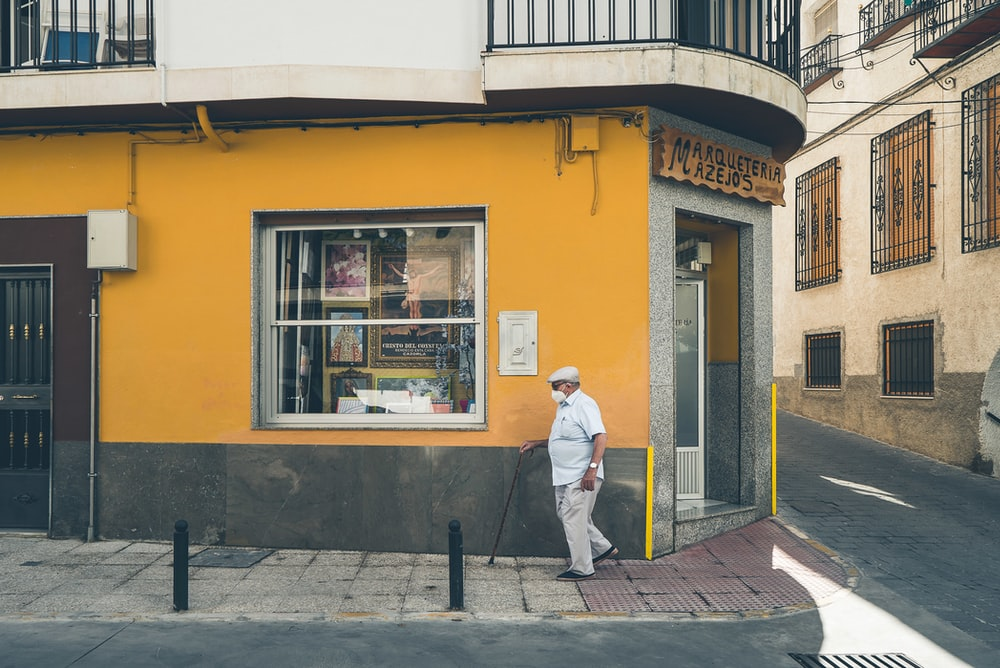 man in white dress shirt and blue denim jeans standing in front of yellow painted building
