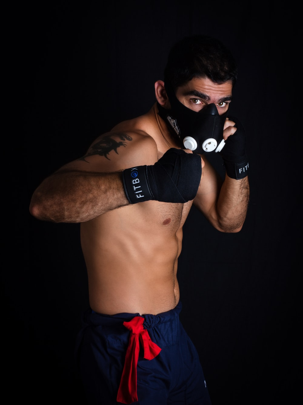 topless man wearing black boxing gloves