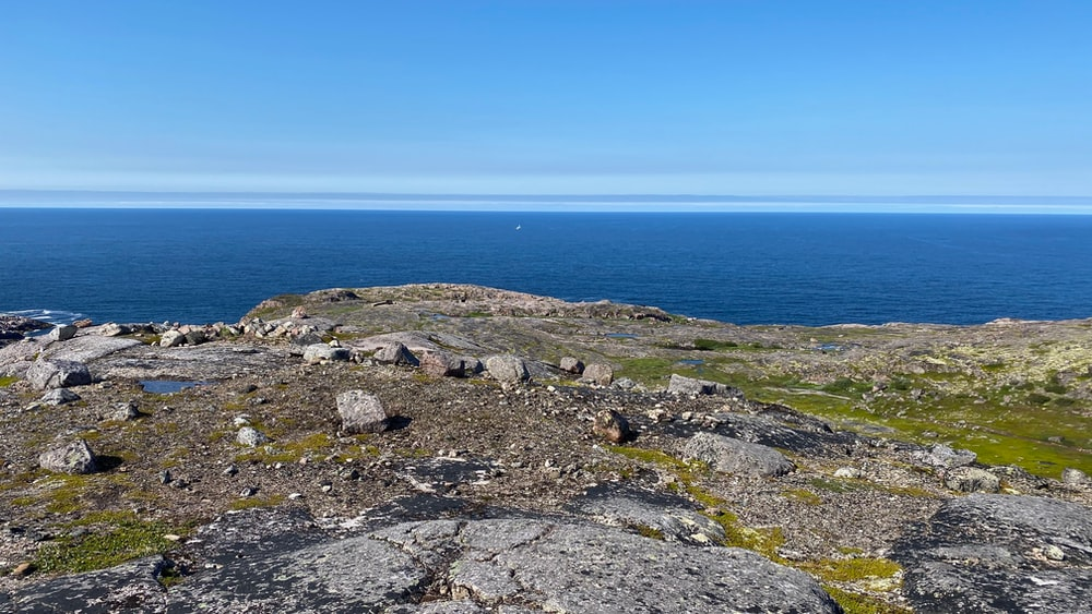 gray rocky mountain beside blue sea under blue sky during daytime