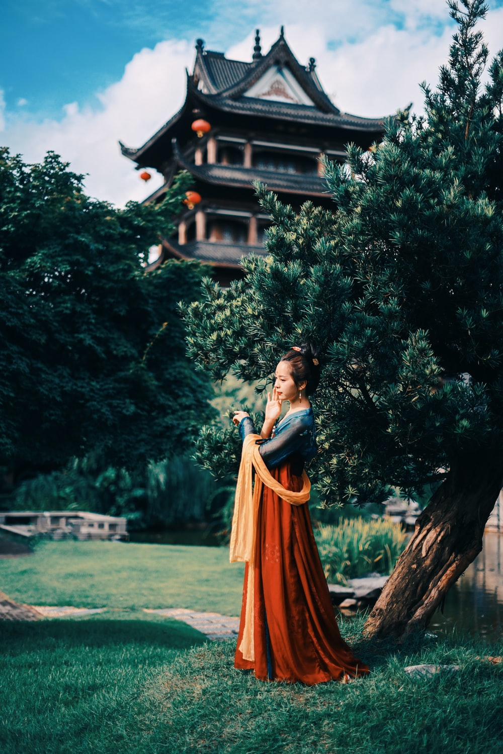 woman in orange dress standing near brown wooden house during daytime