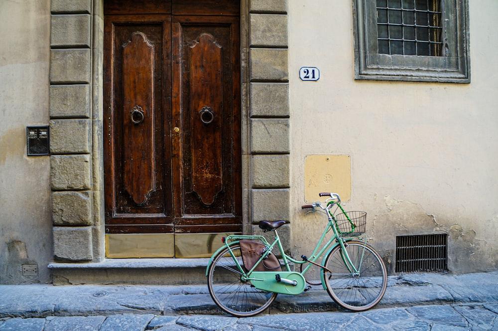 green city bicycle beside brown wooden door