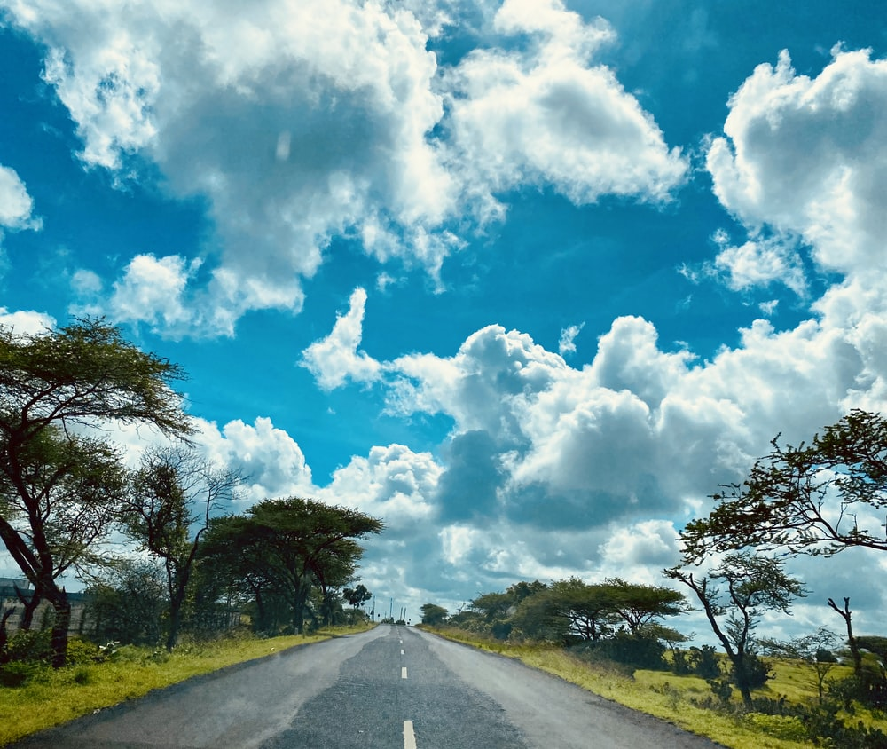 gray asphalt road between green grass field under blue and white sunny cloudy sky during daytime