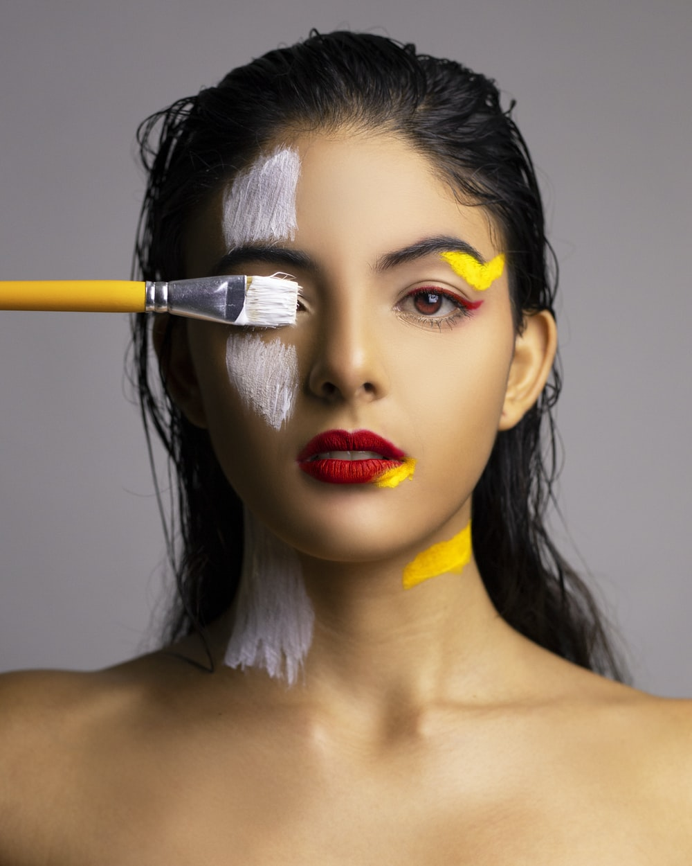 woman with red lipstick holding yellow paint brush
