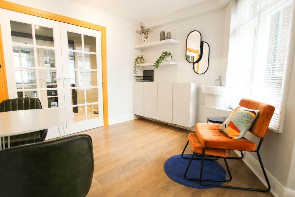brown wooden framed black padded armchair beside white wooden cabinet