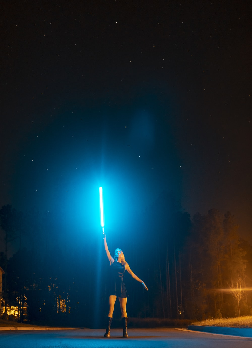 man in black shirt and pants standing on rock during night time