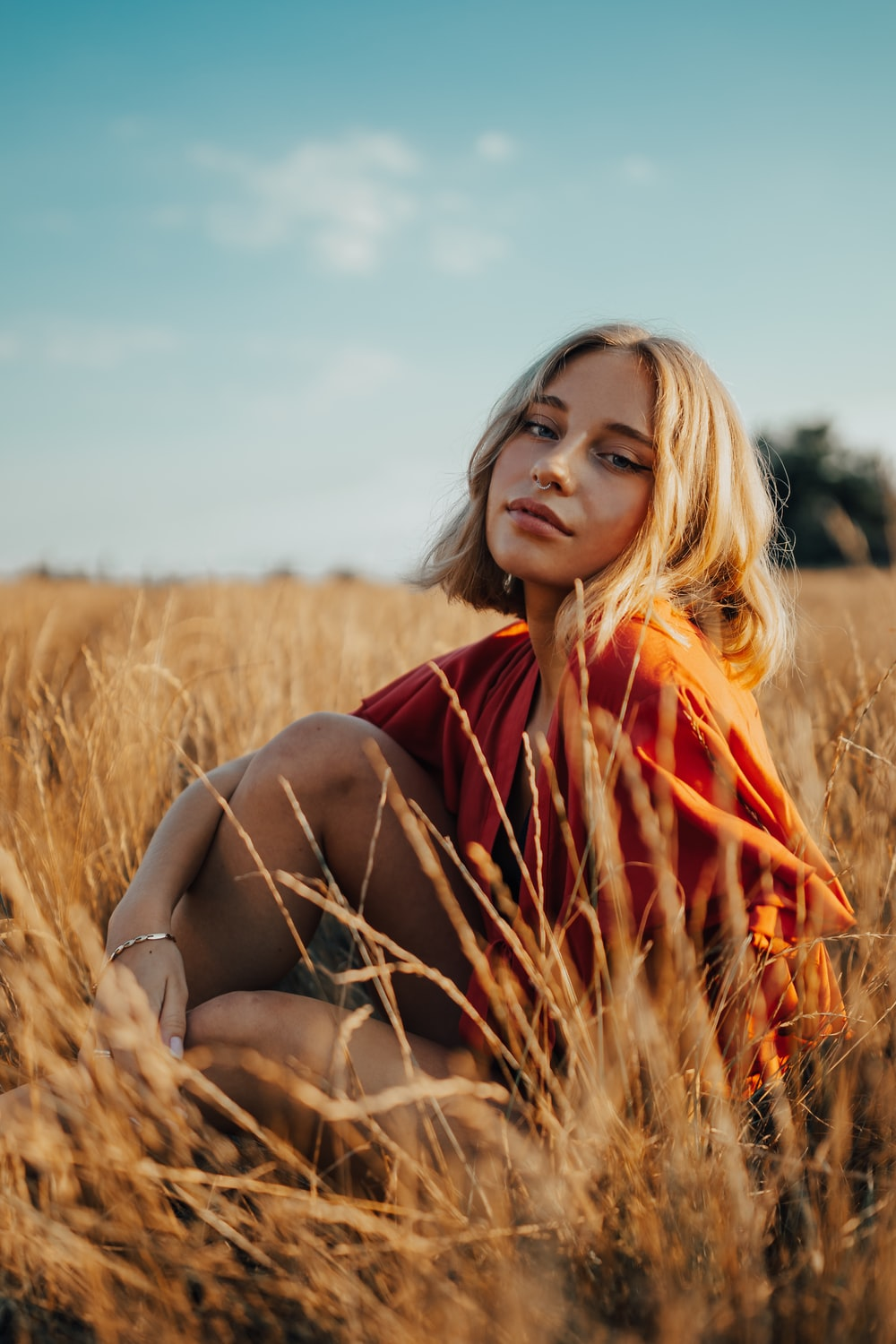woman in red and black plaid scarf sitting on brown grass field during daytime