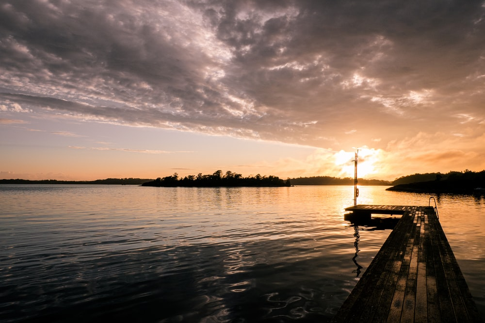 silhouette of a boat on water during sunset
