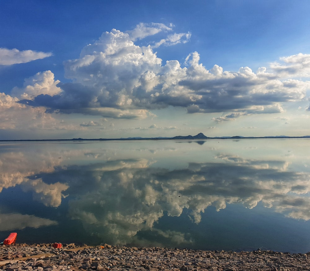 calm water under white clouds and blue sky during daytime