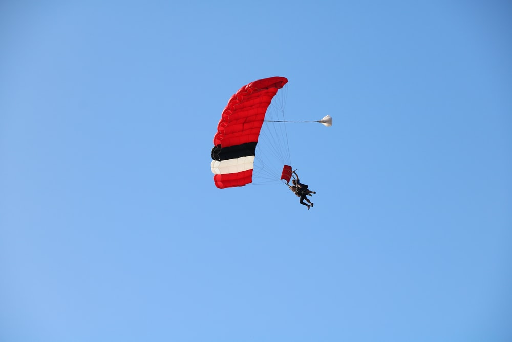 person in red parachute under blue sky during daytime