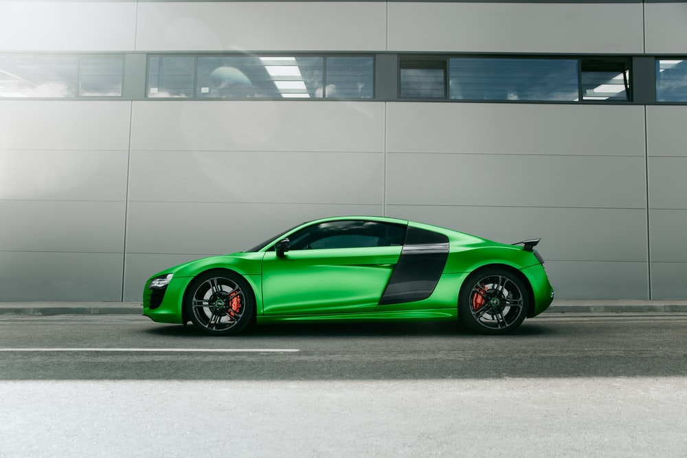 green porsche 911 parked in front of white building