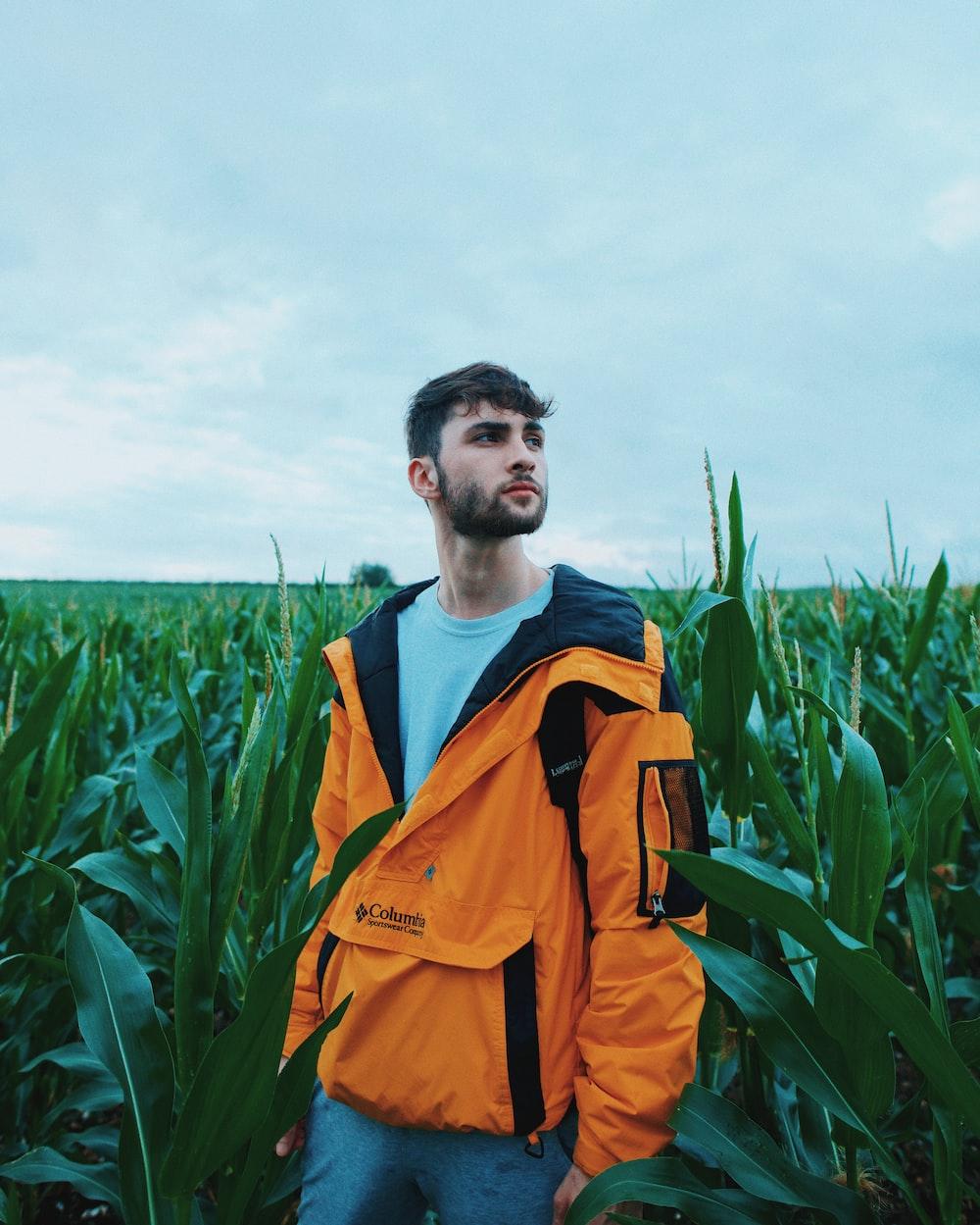 man in orange jacket standing on green grass field during daytime
