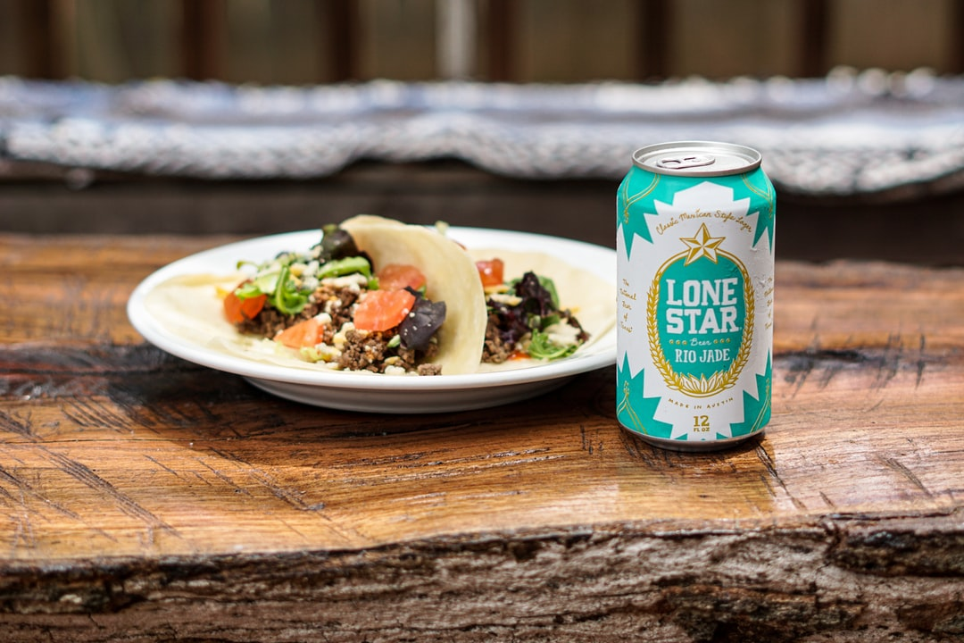 Plate of beef tacos on flour tortillas with a cold Lone Star Rio Jade beer on top of a rustic wood outdoor table