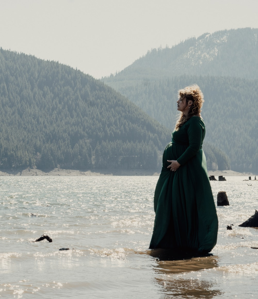 woman in green dress standing on seashore during daytime