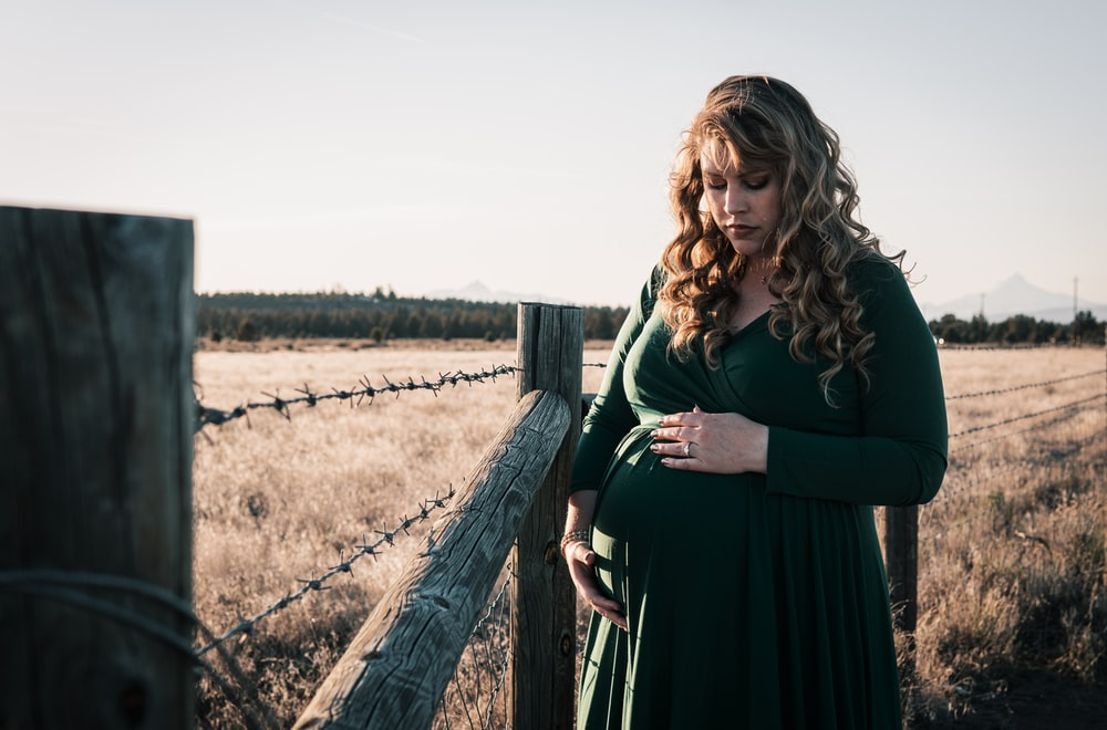woman in black dress standing beside brown wooden fence during daytime