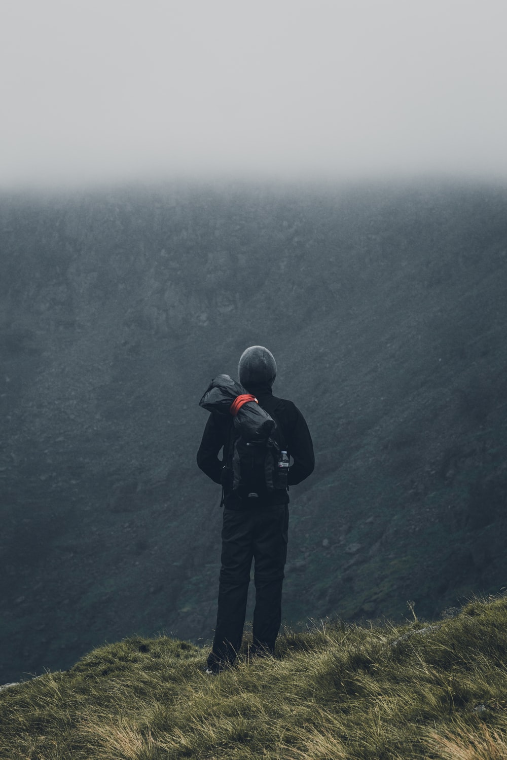man in black jacket and black pants standing on cliff