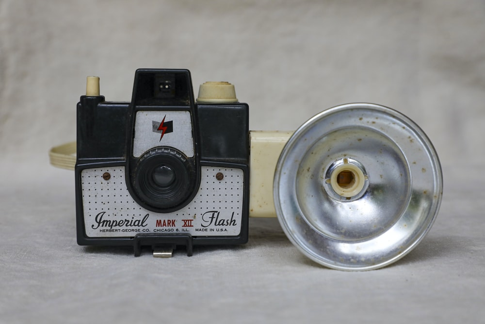 black and silver camera on white table