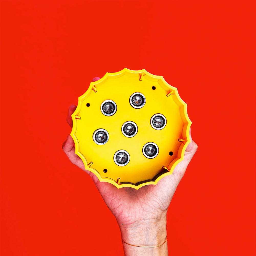 person holding green and yellow polka dot cupcake