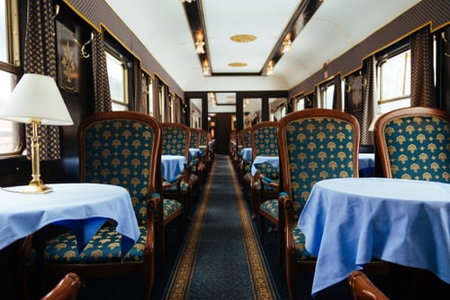 Inside the Orient Express with blue seats and laid tables