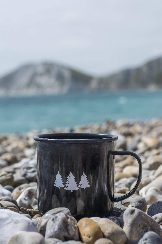 black and white ceramic mug on rocky shore during daytime