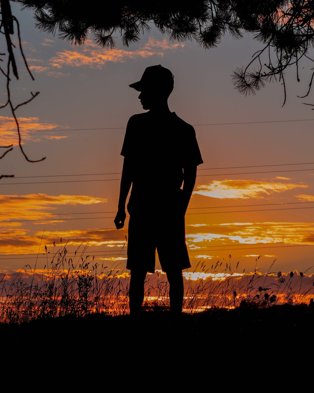 silhouette of person wearing hat standing on grass field during sunset