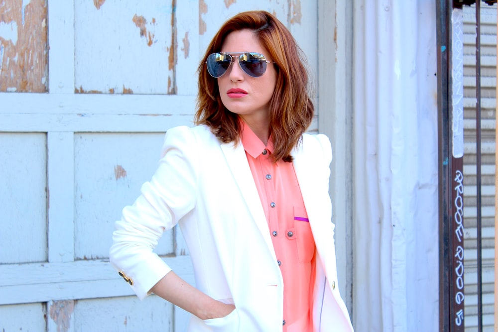 woman in white blazer wearing brown sunglasses