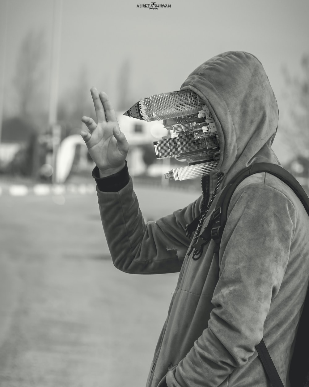 person in black hoodie holding camera