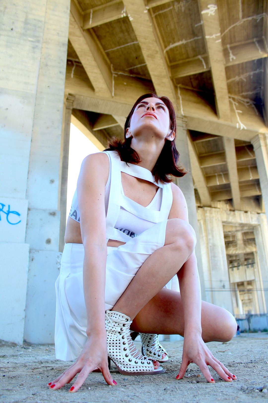 girl crouches under a bridge