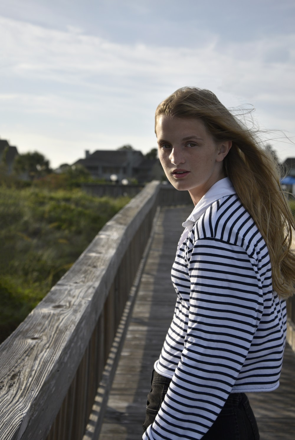 woman in white and black striped long sleeve shirt standing on gray concrete bridge during daytime