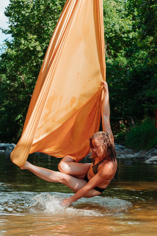 woman in black bikini sitting on brown sand near body of water during daytime
