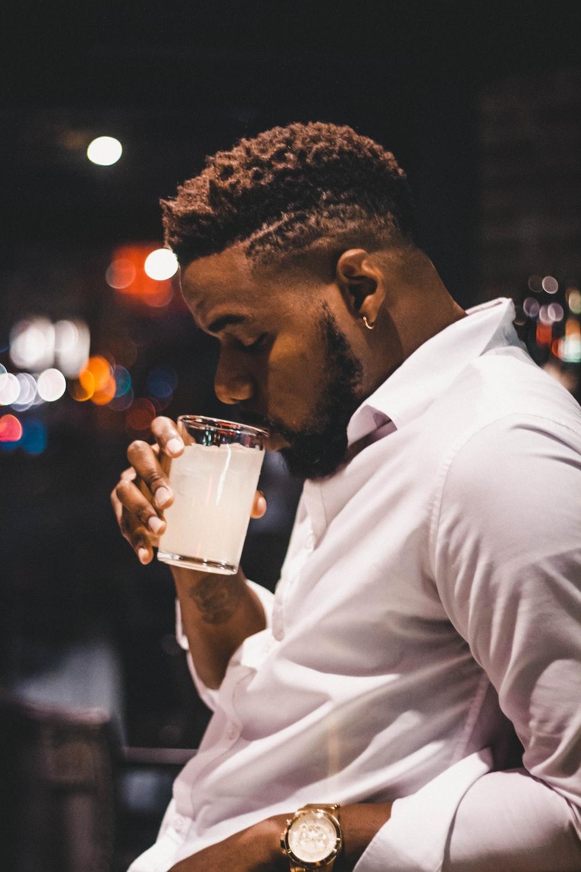 man in white dress shirt drinking beer