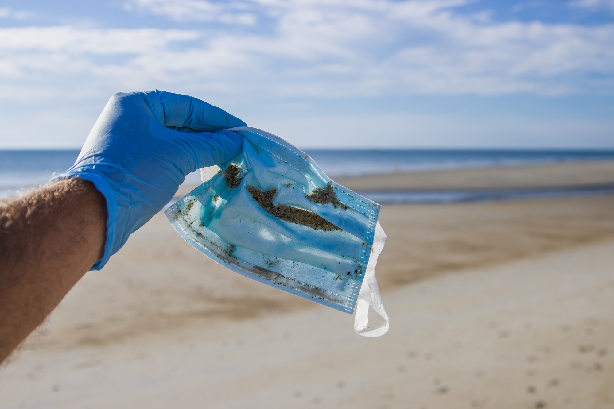 A face mask found during a beach cleanup in Hampton Beach, New Hampshire. During the summer, seasonal beaches are overrun with visitors, and we find overwhelming amounts of single use plastics littered across the sand. We've been finding more and more of this personal protective equipment (PPE) since Coronavirus emerged. You can help by leaving the beach cleaner than you found it, and making small changes to your everyday life. Respect the ocean. Follow on Instagram @wildlife_by_yuri, and find more free plastic pollution photos at: https://www.wildlifebyyuri.com/free-ocean-photography