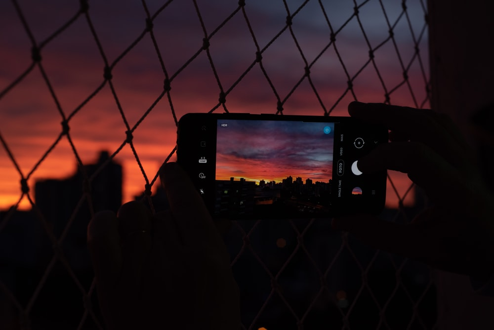 person taking photo of city skyline during night time