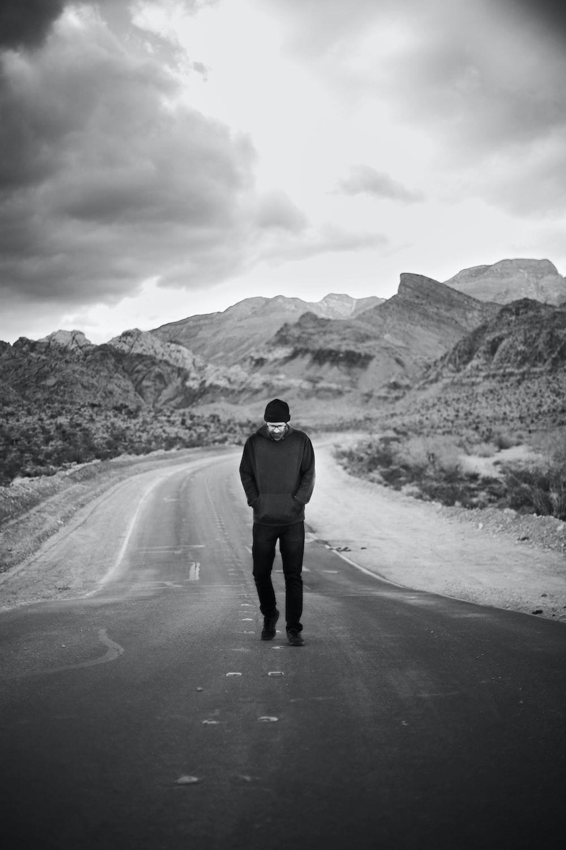 man in black jacket walking on road