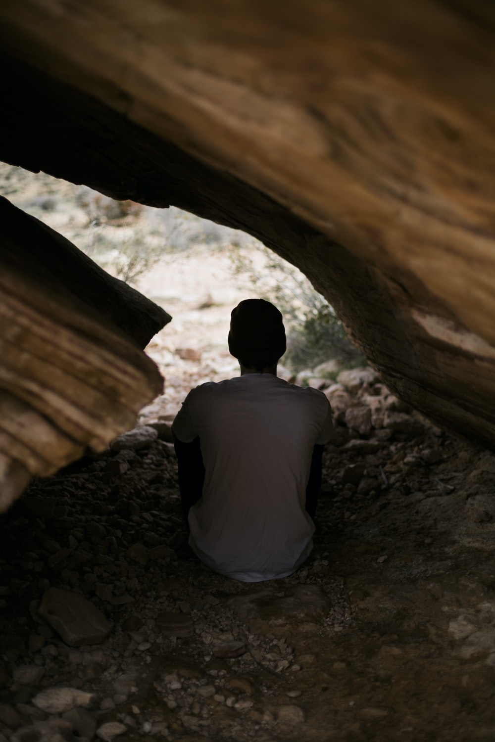 man in white shirt sitting inside cave