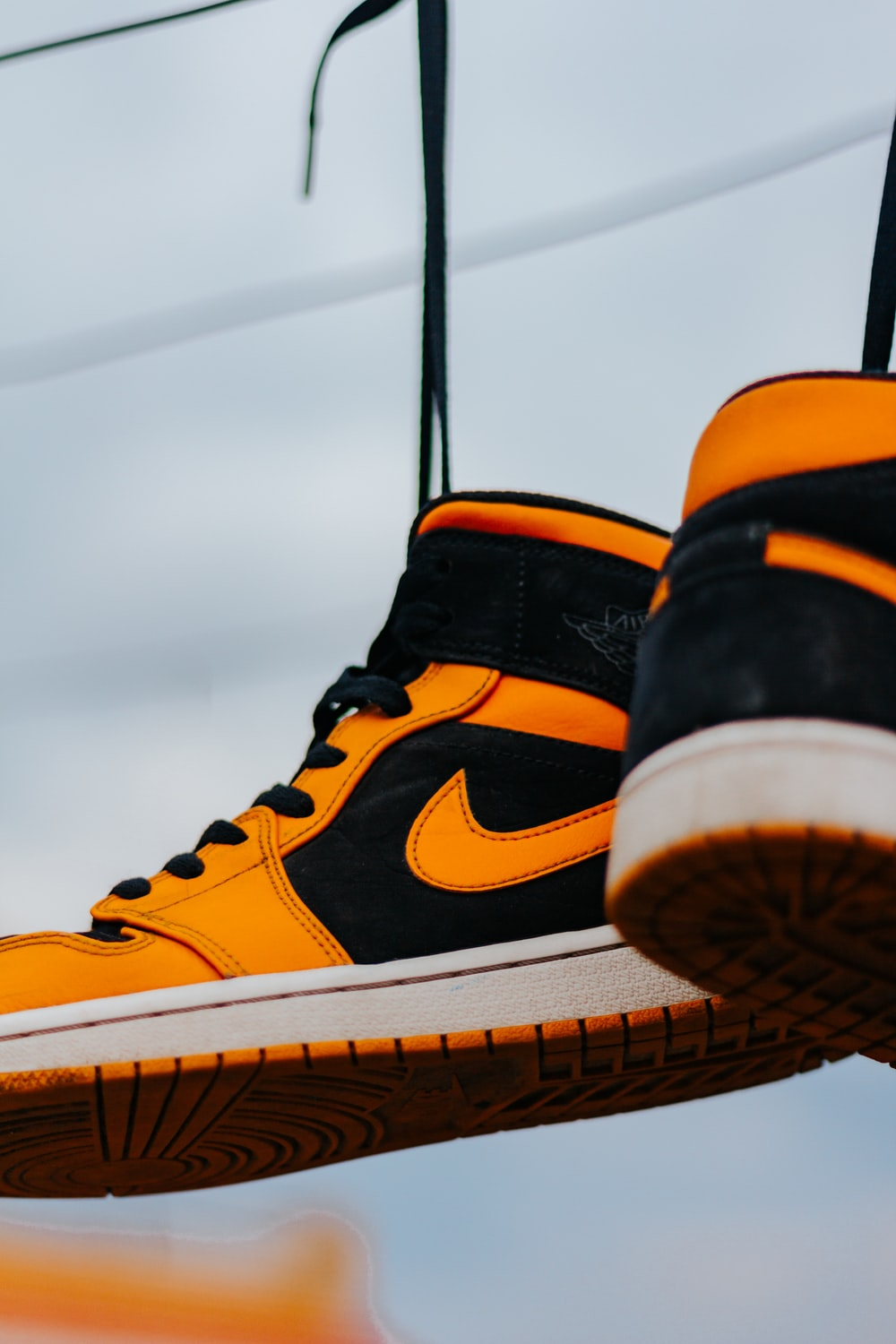 person wearing orange and black nike high top sneakers