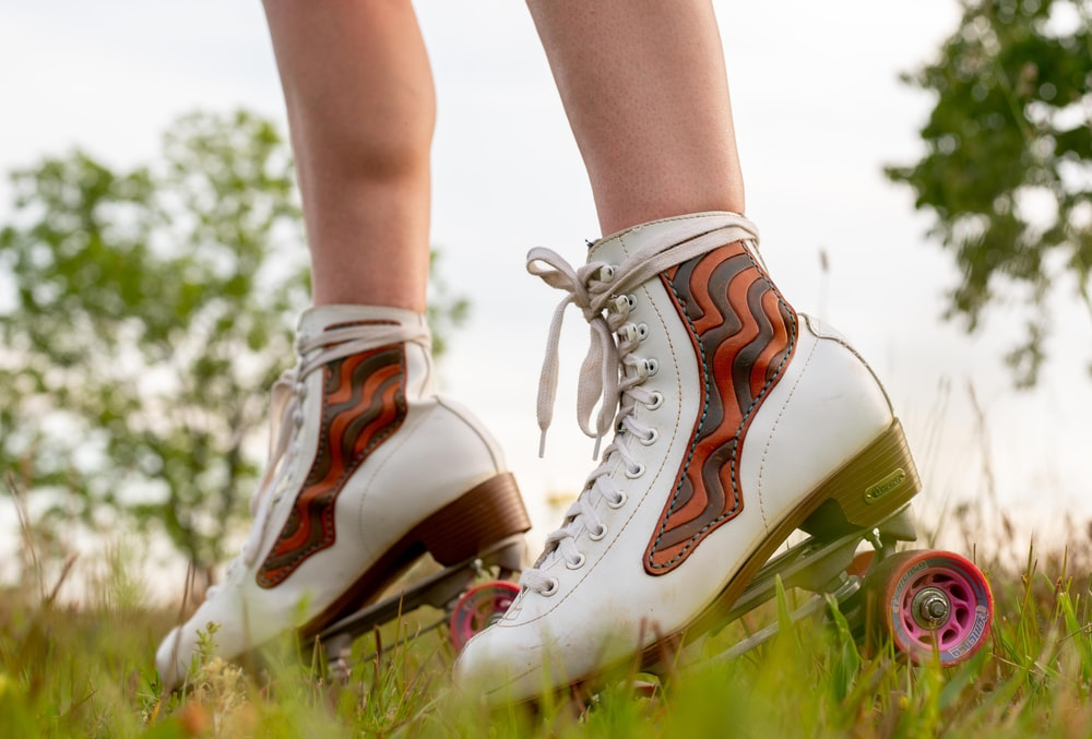 person wearing white converse all star high top sneakers standing on green grass during daytime
