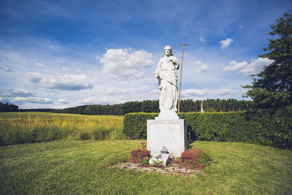 statue of man on green grass field under blue sky during daytime