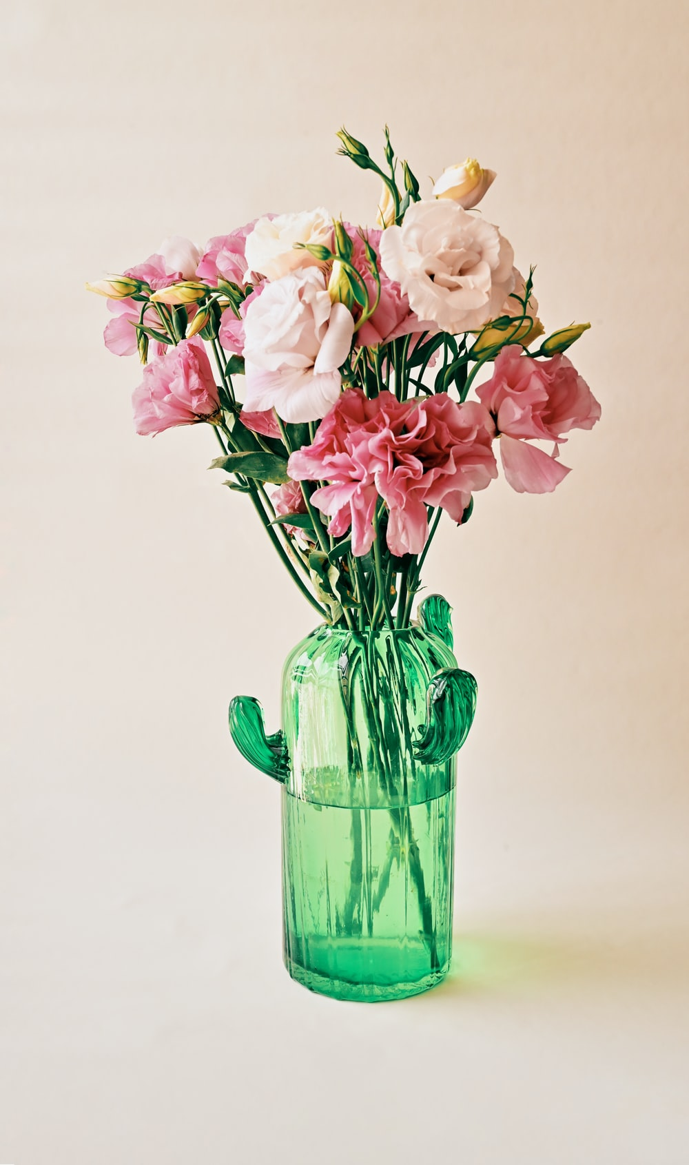 pink and white flowers in green glass vase