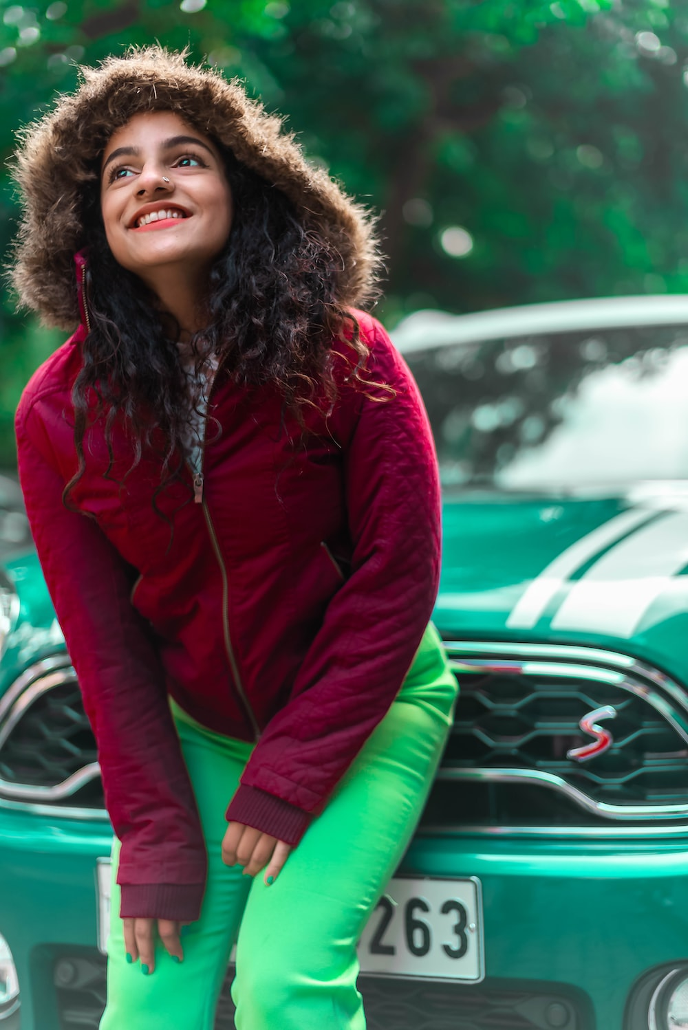 woman in red zip up jacket and green pants sitting on green car hood during daytime