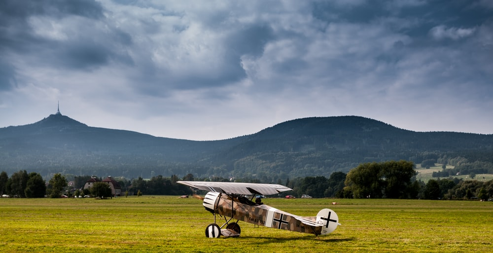 white and black plane on green grass field during daytime